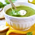Spinach creamy soup in a white bowl on light background.